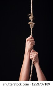 A person hanging from a frayed rope