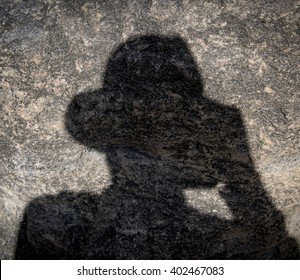 person in hat shadow rock background bank banking creepy isolated unknown stranger concept looking down ground wall