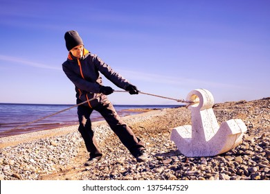 A person hauling the rope with large  anchor. Hard work concept. Ineffective working process. Stupid work abstraction.