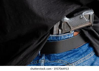 A person is hiding a handgun under the denim belt. Hided handgun under the denim belt.