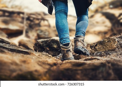 Person is hiking a hill - hiking shoes from behind on a hiking trail