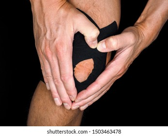 Person holding around knee after injury, taped with black support tape, at close-up isolated on black
