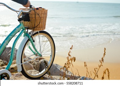 Person holding bicycle on natural beach outdoors background. Closeup image