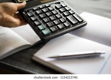 a person holding a calculator above notebook