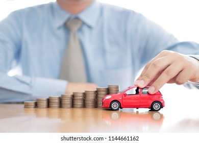 Person Holding Car Over Rising Stacked Coins