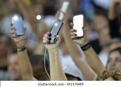 Person holding a cellphone with the flash on and hands up