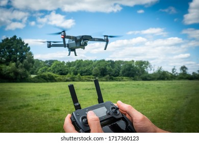 A person holding controller piloting a drone in safe open field