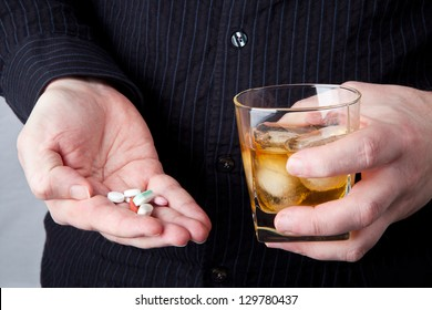 A person holding a glass of alcohol and a handful of pills.