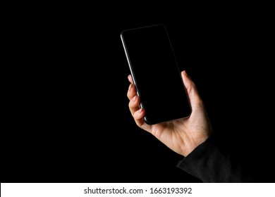 Person holding in hand mobile phone, isolated on black background