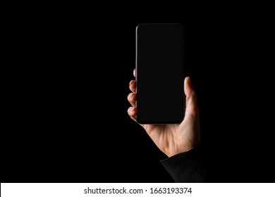 Person holding in hand smartphone, isolated on black background