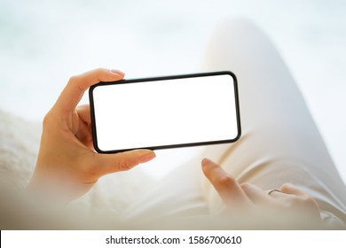 Person holding in hands mobile phone horizontally with empty white screen, mockup photo of smartphone for your own design - Shutterstock ID 1586700610