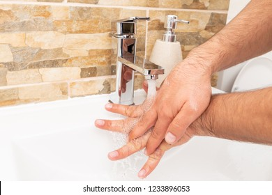 Person holding hands under water from inox tap for rinsing in white sink