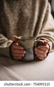 Person holding a hot beverage in a ceramic mug.