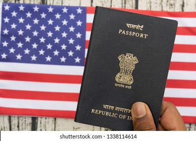 Person holding Indian Passport with hand on a US or american flag as background.