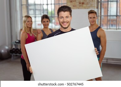 Person holding large blank white poster with other people in background at small fitness gymnasium