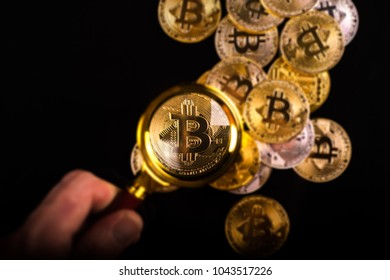 Person holding magnifying glass and looking through it on new virtual money golden bitcoin placed on a black background.