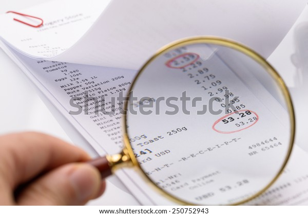 Person Holding Magnifying Glass On Receipt With Red Circle Made On Total Amount