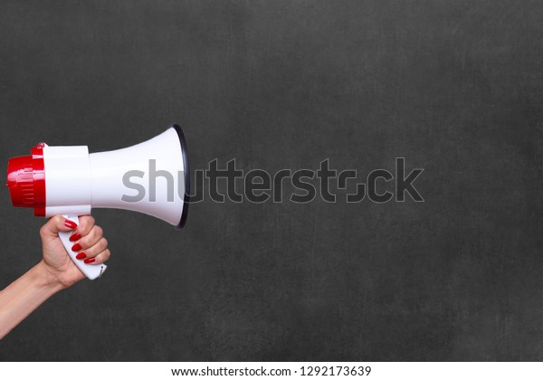 Person holding a megaphone, bullhorn or loud hailer to the side over a blank chalkboard with copy space