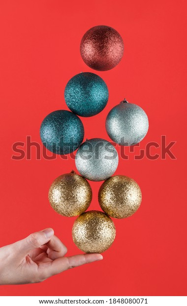 Person holding with one finger different brightly colored Christmas spheres striking a balance on a red background. Christmas decorations. Christmas wallpaper