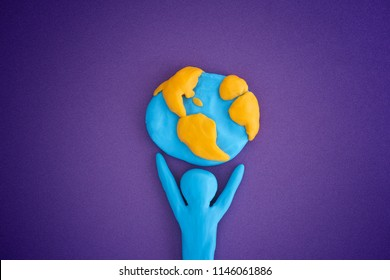 Person holding planet Earth. Person and planet Earth are made out of play clay (plasticine).