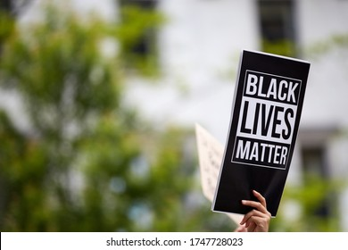 "A person holding a printed black sign ""black lives matter"" at a racially oriented rally. A blurred building and trees in the background"
