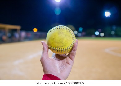 A person holding s softball in front of a softball field at night.