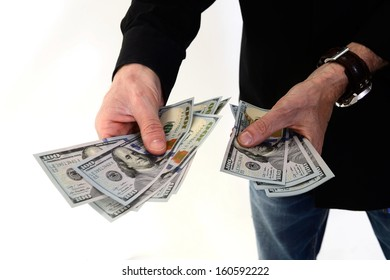 Person holding several new hundred dollar bills shot on white background.  This newly redesigned US currency was released for circulation in October of 2013.
