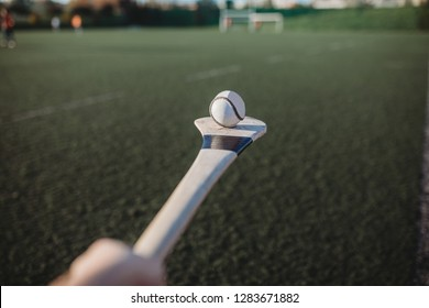 Person holding sliotar on hurl, gaa games