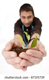 A person holding a small plant in hands
