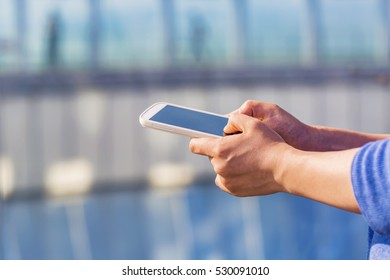 Person holding a smartphone on a blue industrial city background