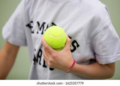 a person holding tennis balls