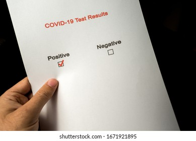 Person holding test results for corona virus, positive