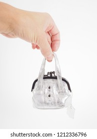 Person holding a tiny silver purse isolated on white