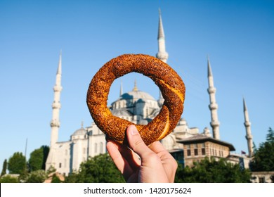 The person is holding a traditional Turkish fast food bagel called Simit against the background of the Blue mosque in Istanbul.
