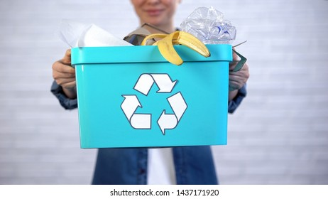Person holding trash bin with disposable and plastic garbage, waste sorting