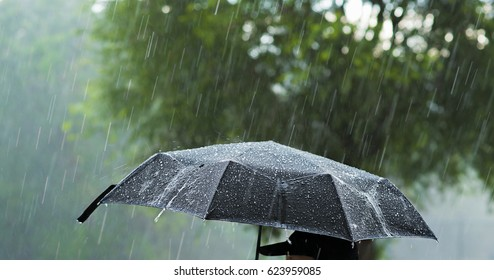 A person holding an umbrella under heavy rain.