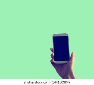 Person holding a white smartphone on a solid colored background