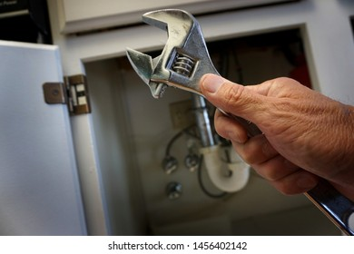 Person holding wrench ready to do plumbing work under sink