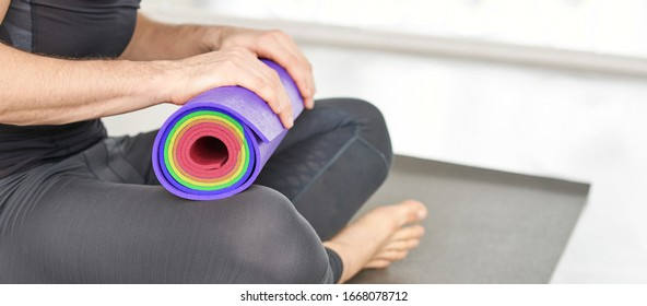 Person holding yoga mat at knee. Sport equipment concept. Pilates teacher with rolled color workout equipment. Man fitness health mockup. Copyspace banner