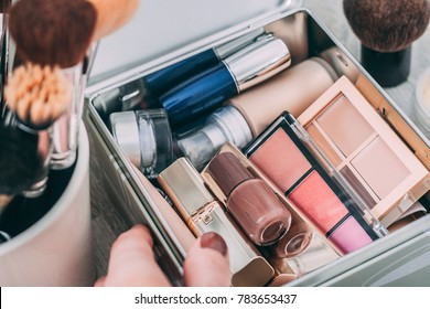 A person holds box with decorative cosmetic. Concealer, blush, foundation, lipsticks, nail polish.
