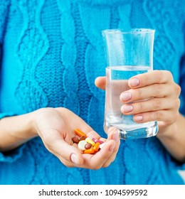 The person holds the medicine and a glass of water in his hands. Square. Concept illness, colds, cure, fall and winter.