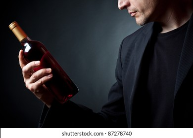 The person holds a red wine bottle in a hand