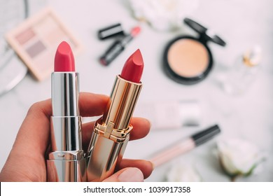 A person holds two lipsticks. Beauty products blurred background. Top view. Copy spase.