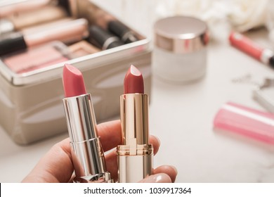 A person holds two lipsticks. Beauty products blurred background. Copy spase.