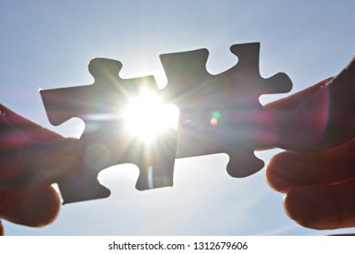 A person holds two puzzle pieces in his hand that fit together, in the background the sun shines and illuminates the parts from behind - concept for brainstorming in the professional environment