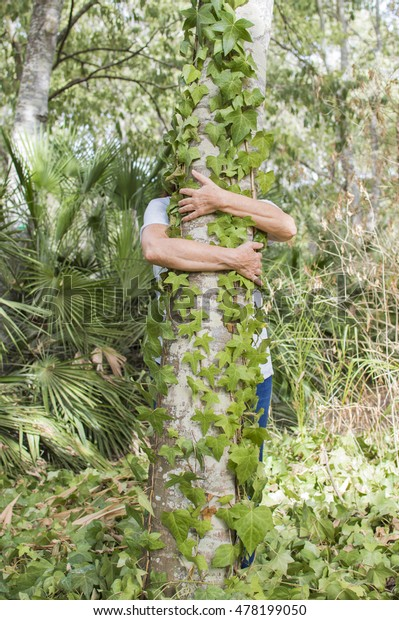 Person hugging tree, person behind the tree, the person's arms around the tree
