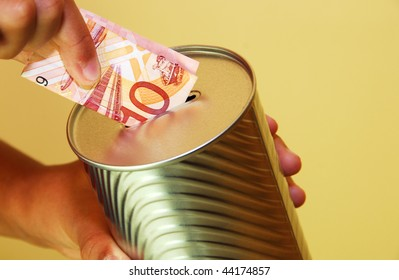a person inserting a  malaysian ten dollar dote in to a silver colored tin can