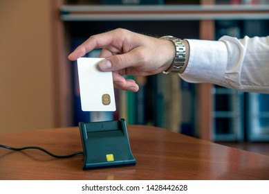 Person inserting smart card with digital certificate in a smart card reader