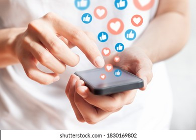 Person interacting on social media network with smartphone by liking and loving posts. Advertising on mobile phone by collecting user data and targeting profiles