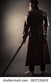 person in jacket with sword standing back